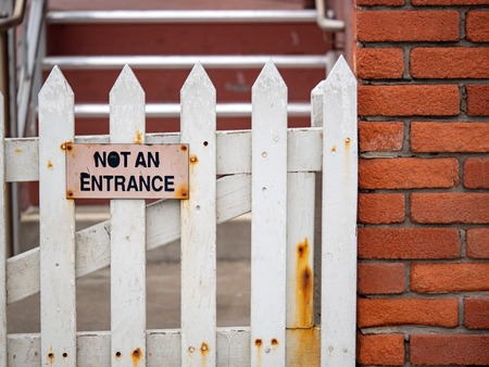 Not an entrance sign on white picket fence with rusted parts on brick building