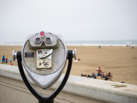 Tower viewer telescope and binoculars looking off to ocean and beach on overcast day with storm coming Banque d'images