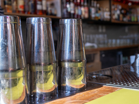 Multiple steel drink shakers sitting on bar countertop ready to make cocktails Imagens
