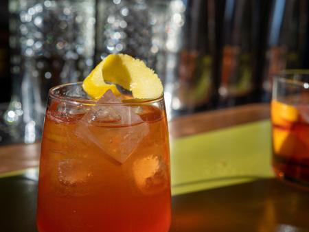 Orange spritz drink with ice cube and lemon peel