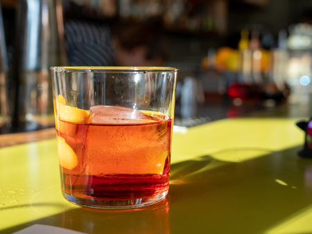 Negroni drink sitting on green bar counter top