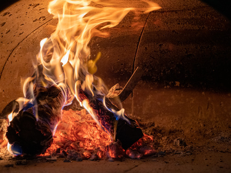 Burning logs, ashes, and intense flames in concrete oven Stockfoto
