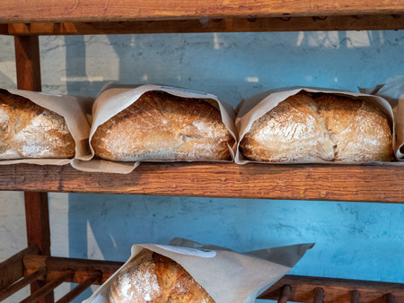 Shelf holding rows of baked and packaged loaves of bread in a bakery