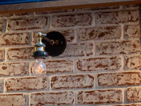 Incandescent rustic light bulb with stylized filament hang on brick wall empty space to rightv Banco de Imagens