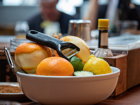 Oranges, limes, and lemons for peeling sitting in a bowl on bar to create drinks