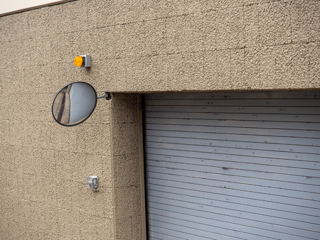 Safety mirror on corner of parking garage complex building entrance