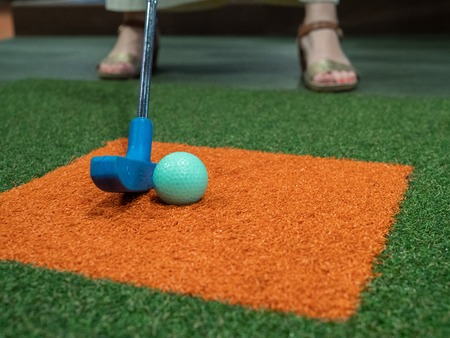 Blue putter on turf lined up next to green golf ball on miniature golf course with woman playing Banque d'images - 124758634