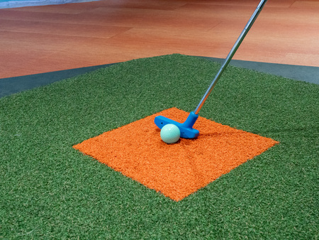 Blue putter on turf lined up next to green golf ball on orange turf on miniature golf course Banque d'images - 124758635