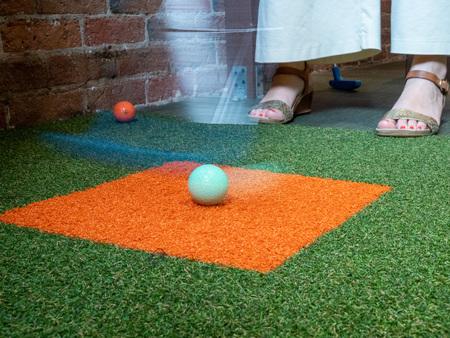 Frau spielt Minigolf und schlägt Ball mit einem Putter in der Mitte des Schwungs Standard-Bild