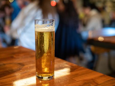 Tall skinny glass of golden lager beer sitting on bar counter Imagens