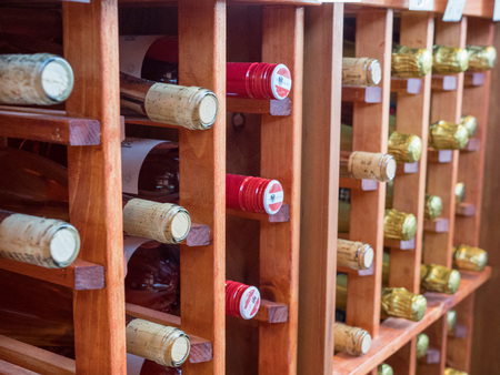 Rows of bottles of red and white wines on wooden wine rack