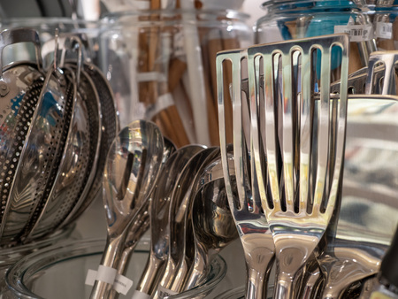Chrome, metal fish spatula on display on rack with other utensils