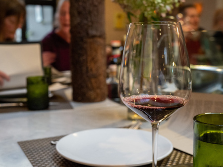 Glass of red tasting wine in restaurant with patrons dining