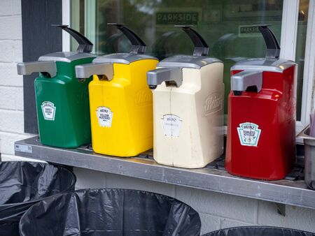 Large commercial dispensers of Heinz ketchup, mustard, relish, and mayonnaise outside for hot dogs and hamburgers