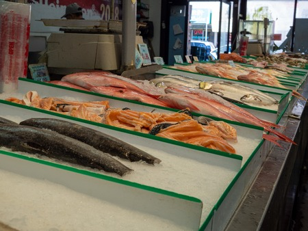Types of fresh fish sitting on ice in grocery store seafood section for purchase