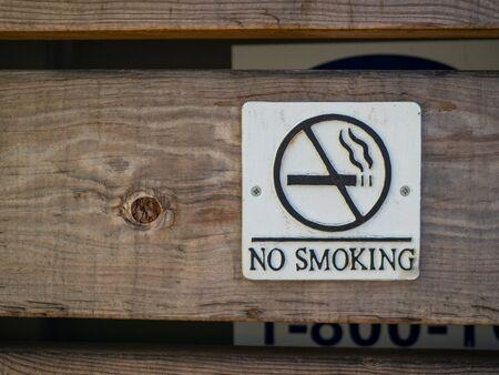 No smoking logo and warning posted on wooden board wall