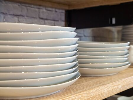 Stack of porcelain plates stacked in two piles on kitchen shelf