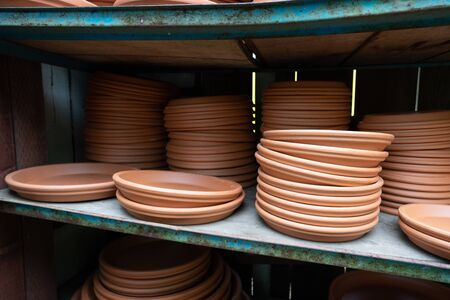Stack of brown planter saucers on shelves at outdoor nursery
