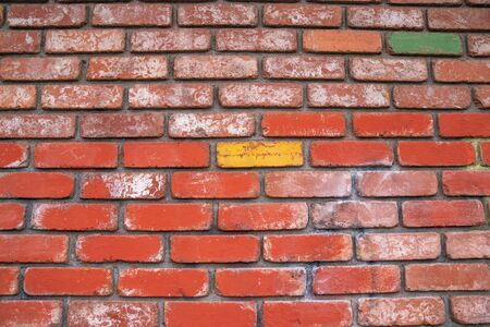 Outdoor brick wall with yellow brick standing out and centered in middle