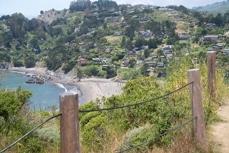 Wooden and wire fence with beach town with houses on hill next to ocean Stock fotó