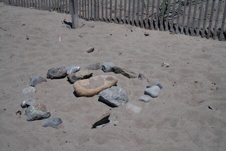 Circular rock formation on beach near fence, tourist and relaxation area