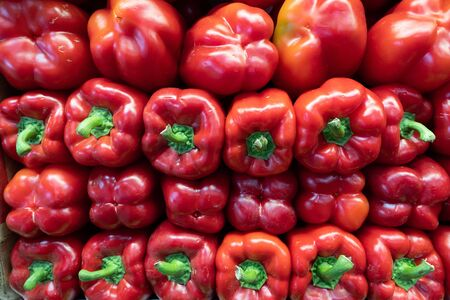 Red bell peppers piled high on sides in grocery store Stock fotó