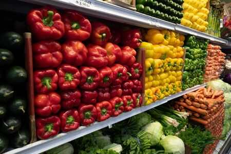 Bell peppers, greens, carrots, cucumbers, lettuce, vegetables in produce section of grocery store