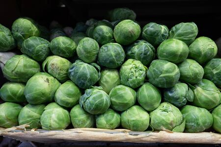 Mound of fresh brussels sprouts for sale in produce section at supermarket