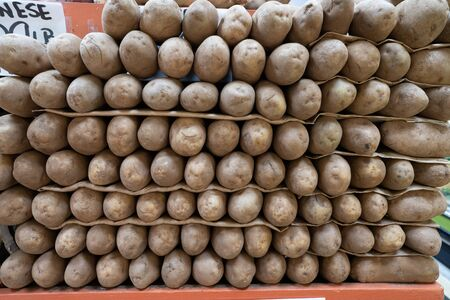 Russet potatoes piled high in produce section in clean supermarket