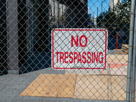 No trespassing sign behind chain link fence blocking off urban construction zone Stock fotó