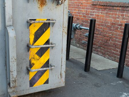 Warning tape pattern on waste container outside at side of building