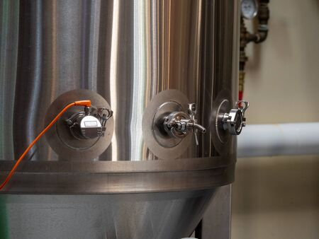 Stainless steel fermentation tank producing beer at a brewery