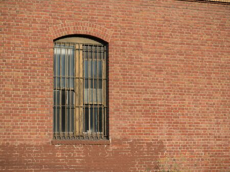 Rusty gated window outside of brick warehouse