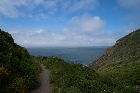 Hiking path trail with rocky cove leading to ocean and blue skies
