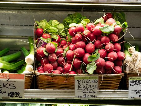 Large bunch of fresh radish from California on grocery store shelf