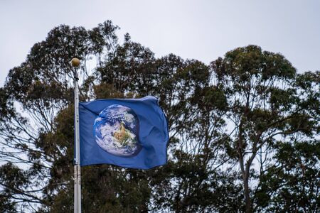 Flag with earth globe satellite picture waving in wind on overcast sky Stock fotó