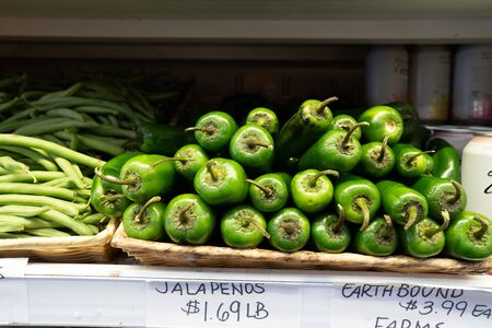 Jalapenos sitting in basket on shelf in grocery store produce section