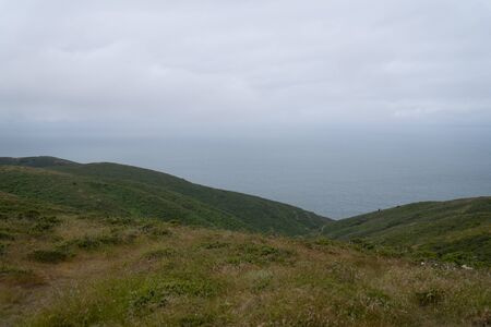 Green hills, hiking path leading to the Pacific ocean on overcast day