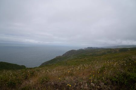 Hills and path leading to endless ocean on cloudy, rainy day