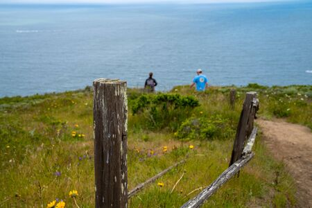 Man and woman hiking on path past wooden fence with fence in focus Stock fotó