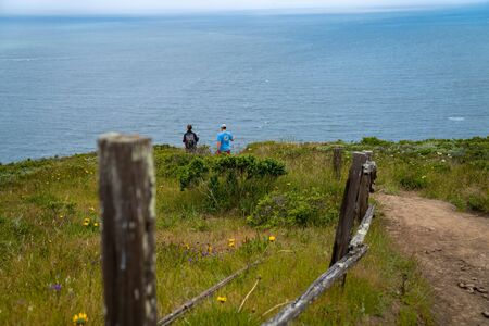 Man and woman hiking on path past wooden fence with background in focus