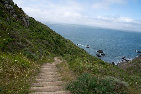 Outdoor dirt stairs on trail path leading down to ocean water