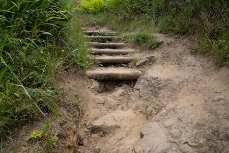 Rocky stair path on dirt trail falling apart with weeds