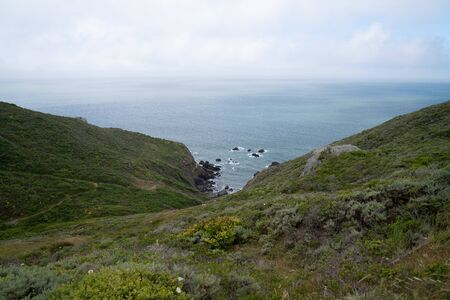 Rolling hills and hiking path lead down into a rocky cove in the ocean