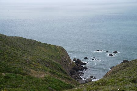 View from top of hills leading to rocky cove in the ocean