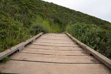 Small wooden bridge leading on hiking trail connecting grassy hills