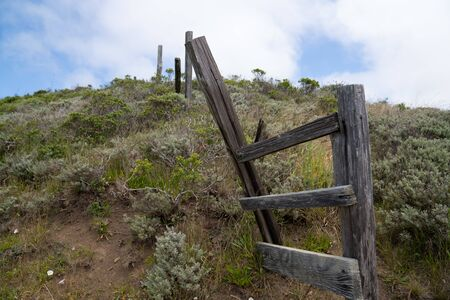 Broken and rustic wooden fence sitting on grassy hill in hike trail
