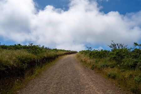Winding dirt trail road going into horizon with clouds in nature Stock fotó