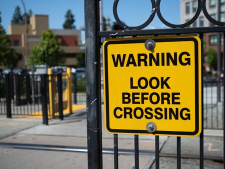 Warning look before crossing yellow warning sign at train station