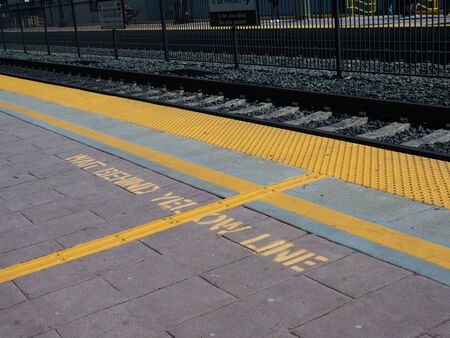 Wait behind yellow line warning on ground on train platform